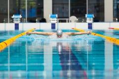 Dynamische en geschikte zwemmer die in GLB uitvoerend de vlinderslag ademen royalty-vrije stock afbeeldingen