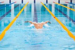 Dynamische en geschikte zwemmer die in GLB uitvoerend de vlinderslag ademen stock afbeelding