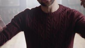 Dynamische Kamera zeigt junges Braun gemusterten Mann im Pullover, der im leeren Raum klopft stock video footage