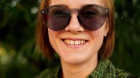 Dynamische video Een close-upportret van een roodharig meisje in zonnebril tegen de achtergrond van de zomergreens naughty stock video