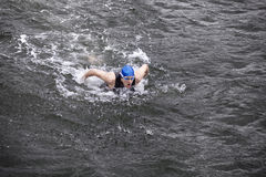 Dynamischer und geeigneter Schwimmer, der den Schmetterlingsanschlag im dunklen Ozeanwasser durchführt Lizenzfreies Stockfoto