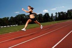 Dynamisches Bild einer jungen Frau, die auf eine Spur läuft Lizenzfreies Stockfoto