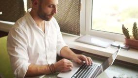 Dynamisches Portrait Ein Mann in einem weißen Hemd arbeitet im Internet durch einen Laptop Finanzadvisory stock video footage