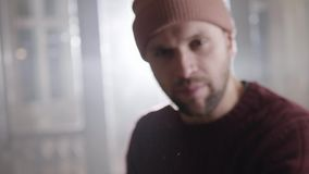 Dynamisches Video des jungen bärtigen Mannes in Braun gestrickter Strickjacke und in der Kappe, die Pochen tut stock footage