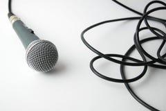 Dynamisk mikrofon med kabel på vit bakgrund Arkivfoto