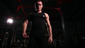 Dynamisk rörelse av kameran, en man i svart sportswear drar på stången, då går till övningen med stången arkivfilmer