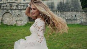 Dynamisk video av en härlig blondin i den vita klänningen arkivfilmer
