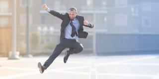 Dynamiskt hoppa för affärsman som är utomhus- royaltyfri fotografi