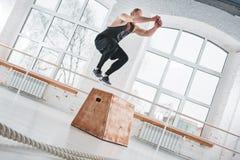 Dynamiskt skott av den färdiga idrottsman nen som hoppar över den arga asken i konditionklubba arkivfoto