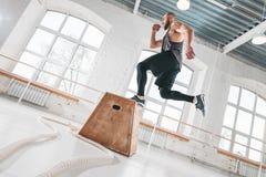 Dynamiskt skott av den färdiga idrottsman nen som hoppar över den arga asken i konditionklubba royaltyfri foto