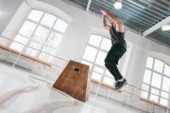 Dynamiskt skott av den manliga idrottsman nen för kondition som hoppar på den fyrkantiga asken i crossfitidrottshall royaltyfri fotografi