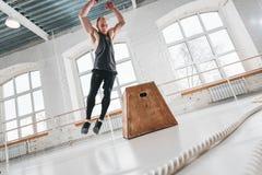 Dynamiskt skott av den manliga idrottsman nen för kondition som igenom hoppar på den fyrkantiga asken i arg idrottshall arkivfoto