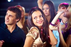 Dynamism. Portrait of cheerful girl dancing at party among her friends Royalty Free Stock Photography