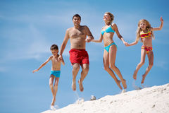 Dynamism. Photo of happy family jumping on sand on summer vacation Stock Photography