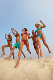 Dynamism. Portrait of happy friends jumping over sandy shore Royalty Free Stock Photos