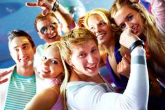 Dynamism. Portrait of glad guy and girl dancing at party with friends on background Royalty Free Stock Photo