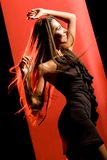 Dynamism. Portrait of beautiful dancer wearing elegant black dress and moving over red background Royalty Free Stock Photo