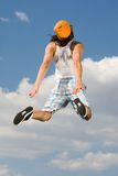Dynamism. Rear view of energetic guy jumping high against bright blue sky Stock Photos