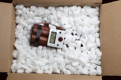 Dynamite Bomb in a Cardboard Shipping Box. Photograph of red sticks of dynamite with a electronic timer in a cardboard shipping box with shipping peanuts stock photography