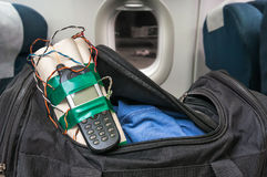 Dynamite bomb with phone in terrorist bag inside airplane. Terrorism concept Stock Image