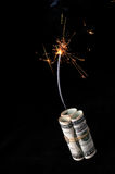Dynamite cash with lit fuse. A roll of cash made into a dynamite stick has a lighted fuse throwing smoke and sparks before it explodes royalty free stock photography