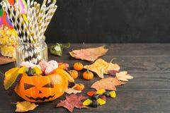 Dyniowa dźwigarka z Halloween cukierkami i jesieni dekoracjami na drewnianym stole obrazy stock