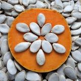 Dyniowi ziarna na pomarańczowym tło kawałku bania, naturalne tekstury i rytm, t Zdjęcia Royalty Free