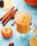 Dyniowy smoothie z pasztetowymi pikantność na turkusowym drewnianym tle Zdjęcia Royalty Free