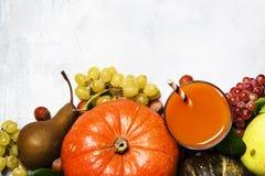 Dyniowy sok, jesieni żniwo warzywa, owoc i dokrętki, dalej fotografia royalty free