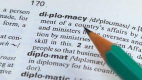 Dyplomacja, ołówkowy wskazuje słowo w słownictwie, stosunek międzynarodowy, biznes zdjęcie wideo