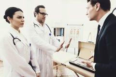 Dyplomowana lekarka odmawia brać ogromną ilość pieniądze od biznesmena lekarstwo dolegliwość łapówka fotografia stock