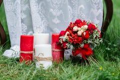 Dyr moderiktig bröllopbukett av rosor i marsala och röda färger som står på gräset nära stora stearinljus Brud- detaljer och de Royaltyfria Bilder