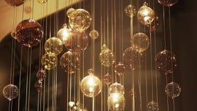Dyr stor ljuskrona av exponeringsglas i en restaurang eller en konserthall Ljuskronabelysning i Hall, Bokeh, ilsken blick, glöd arkivfilmer