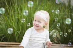 Dyrbar liten flicka som har gyckel med bubblor Royaltyfri Fotografi