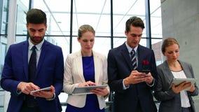 Dyrektory wykonawczy używa telefon komórkowego i cyfrową pastylkę zdjęcie wideo