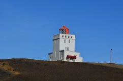Dyrholaey fyr på havsklipporna av Island Arkivbild