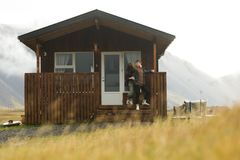 Dyrholaey / Iceland - 26/09/2018: A detached Scandinavian house. A young couple outside of the wooden house in the middle of nowhere stock images
