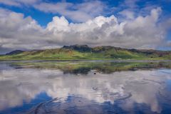 Dyrholaos estuary in Iceland. Reflection in the water of Dyrholaos estuary near cape Dyrholaey in Iceland royalty free stock photos