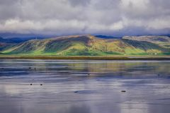 Dyrholaos estuary in Iceland. Reflection in the water of Dyrholaos estuary near cape Dyrholaey in Iceland stock photos
