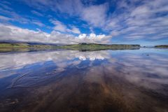 Dyrholaos estuary in Iceland. Reflection in the water of Dyrholaos estuary near cape Dyrholaey in Iceland royalty free stock photo