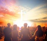 Dyrkanbegrepp: Konturfolk som söker efter korset på soluppgångbakgrund royaltyfria bilder