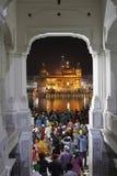 Dyrkare i nattetid på den guld- templet amritsar royaltyfria foton
