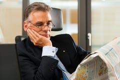 dyryguje jego gazetowego biura czytanie Zdjęcie Royalty Free