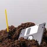 Dyskietka jest połówką zakopującym w ziemi, obok łopaty obraz stock