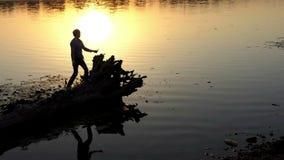Dyskoteka mężczyzna na lasowym jeziornym banku przy złotym zmierzchem zbiory wideo