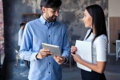 Dyskutować nowego biznesowego projekt Dwa szczęśliwego młodzi ludzie w przypadkowej odzieży uśmiechniętej i patrzeje cyfrową past zdjęcia royalty free