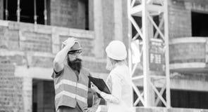 Dyskutuje postępu projekt Inspektorski i brodaty brutalny budowniczy dyskutuje budowa postęp Projekt budowlany obraz stock