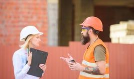 Dyskutuje postępu plan Kobieta inżynier i brodaty brutalny budowniczy dyskutujemy budowa postęp Przemysł Budowlany zdjęcie royalty free