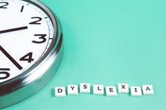 Dyslexi- och läsningsord med en stor klocka arkivfoto