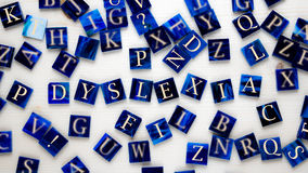 Dyslexia. Mosaic pieces with letters in front of wooden background- DYSLEXIA - selective focus Royalty Free Stock Image